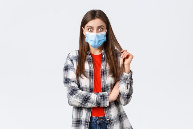 Coronavirus-uitbraak, vrije tijd op quarantaine, sociale afstand en emotiesconcept. geschokt en nieuwsgierig jong meisje met medisch masker en geruit overhemd, staren naar vriend die roddels of verbluffend nieuws vertelt.