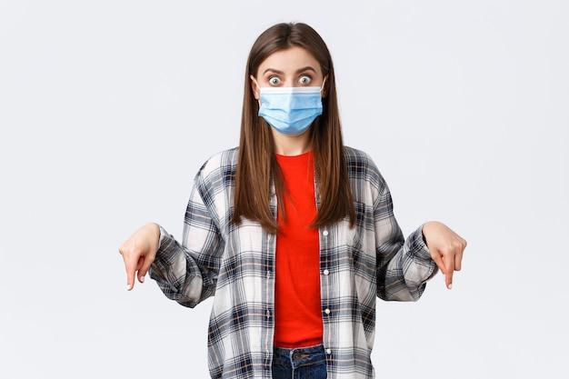 Coronavirus-uitbraak, vrije tijd op quarantaine, sociale afstand en emotiesconcept. geschokt en onder de indruk jonge vrouw in medisch masker en casual outfit, wijzende vingers naar beneden, staren camera