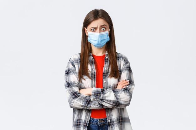 Coronavirus-uitbraak, vrije tijd op quarantaine, sociale afstand en emotiesconcept. geschokt en verward jong mooi tienermeisje hoort vreemd nieuws, trekt verbaasde wenkbrauwen op, draagt medisch masker