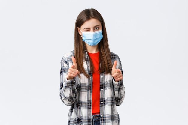 Coronavirus-uitbraak, vrije tijd op quarantaine, sociale afstand en emotiesconcept. je kunt er puntjes op zetten. ondersteunende jonge aantrekkelijke vrouw met medisch masker wijzend op camera, knipoog en feliciteer.