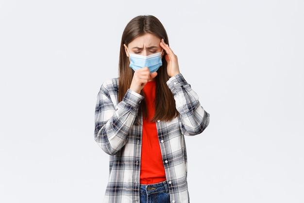 Coronavirus-uitbraak, vrije tijd op quarantaine, sociale afstand en emotiesconcept. jonge vrouw voelt zich ziek, draagt een medisch masker en hoest, raakt de tempel aan als hoofdpijn, hoge koorts.
