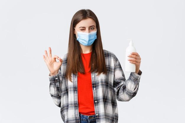 Coronavirus-uitbraak, vrije tijd op quarantaine, sociale afstand en emotiesconcept. leuke blanke vrouw met medisch masker verzekert dat deze zeep goed is voor het voorkomen van virussen, laat een oka-teken zien