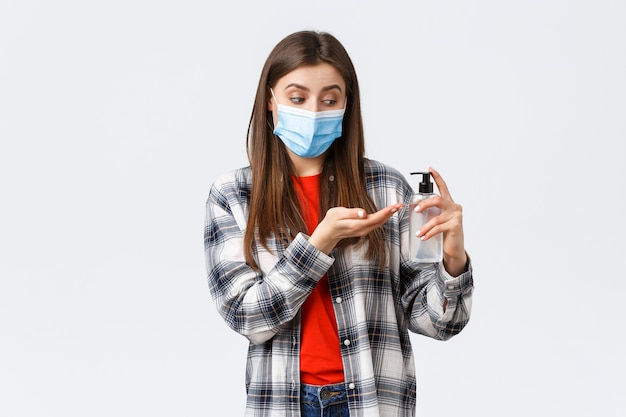 Coronavirus-uitbraak, vrije tijd op quarantaine, sociale afstand en emotiesconcept. leuke vrouw die voor de gezondheid zorgt door preventieve maatregelen te nemen, handdesinfecterend middel toe te passen, een medisch masker te dragen.
