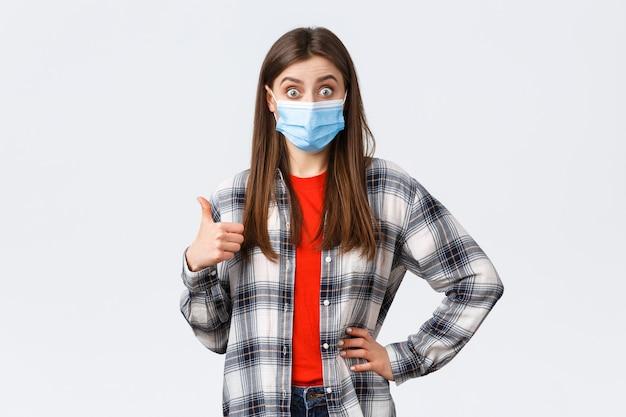 Coronavirus-uitbraak, vrije tijd op quarantaine, sociale afstand en emotiesconcept. opgewonden en verraste jonge vrouw met medisch masker hoort echt goed idee, duim omhoog ter goedkeuring