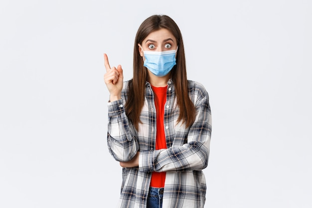 Coronavirus-uitbraak, vrije tijd op quarantaine, sociale afstand en emotiesconcept. opgewonden slimme jonge vrouw met medisch masker en geruit overhemd, wijsvinger opgestoken om suggestie te zeggen, heb een idee