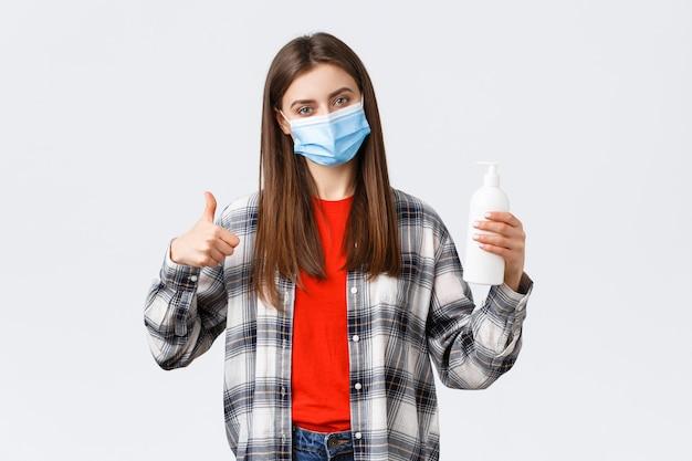Coronavirus-uitbraak, vrije tijd op quarantaine, sociale afstand en emotiesconcept. tevreden vrouwelijke klant, winkelklant met medisch masker adviseert deze handzeep of handdesinfecterend middel, duim omhoog