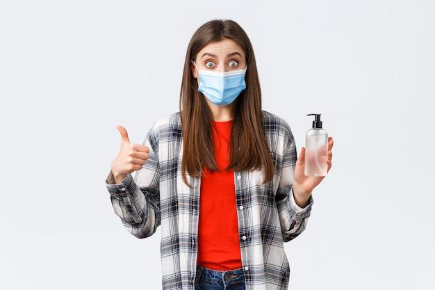 Coronavirus-uitbraak, vrije tijd op quarantaine, sociale afstand en emotiesconcept. verbaasd en onder de indruk meisje met medisch masker, wil voorkomen dat je een virus oploopt, duim omhoog goed handdesinfecterend middel