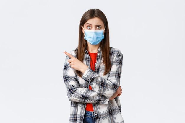 Coronavirus-uitbraak, vrije tijd op quarantaine, sociale afstand en emotiesconcept. verward en bezorgd meisje dat een vraag stelt over iets vreemds, met de vinger naar links wijst, een medisch masker covid-19 draagt.