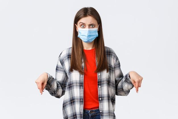 Coronavirus-uitbraak, vrije tijd op quarantaine, sociale afstand en emotiesconcept. verwarde vrouw met medisch masker kan niet begrijpen wat er gebeurt, wijst met de vingers naar beneden, kijkt gealarmeerd.