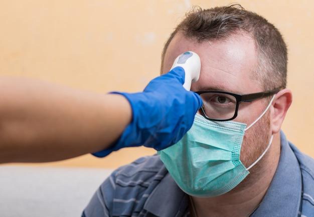 Coronavirus-verpleegster die handschoenen draagt en medische infrarood-voorhoofdthermometer vasthoudt om de lichaamstemperatuur te controleren op virussymptomen.