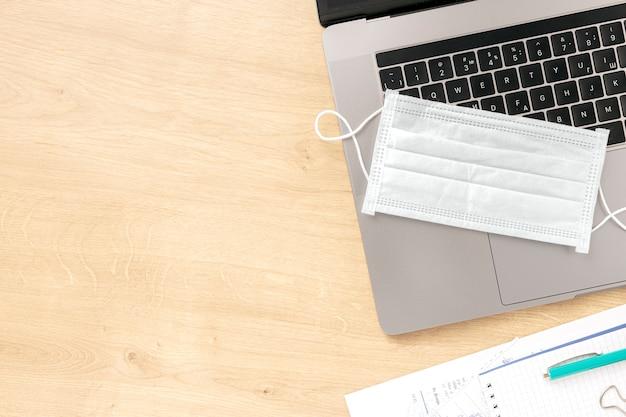 Coronavirus werken vanuit huis concept laptop met beschermend masker op houten tafel met kopie ruimte