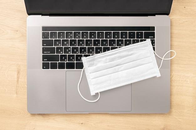 Coronavirus werken vanuit huis concept laptop met beschermend masker op houten tafelblad bekijken