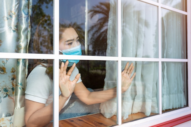 Coronavirus. zieke vrouw van corona virus kijkt door het raam en het dragen van masker bescherming en herstel van de ziekte in huis. quarantaine. patiënt geïsoleerd om infectie nieuw normaal te voorkomen.
