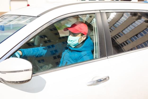 Coronavirusbescherming. taxichauffeur met een beschermend masker en handschoenen. concept: stop: covid-19