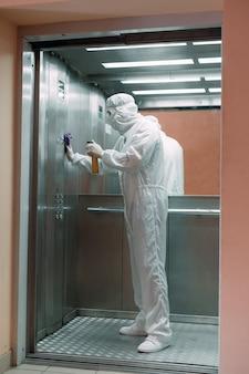 Coronavirusbesmetting. paramedicus in beschermend masker en kostuum die een lift met sproeier desinfecteert,