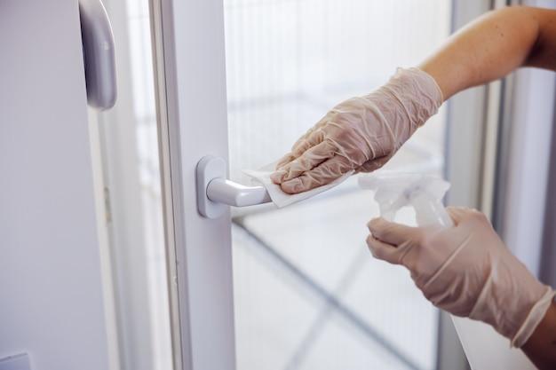 Coronaviruspreventie, schoonmaakster die de deurknop afveegt met antibacteriële reiniger voor het doden van coronavirus op aanrakende oppervlakken.