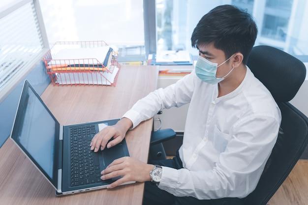 Coronavirusziekte of covid-19-epidemie zakenman met masker, kantoormedewerker werkt en draagt masker om coronavirus te beschermen