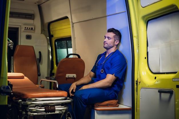 Corpsman in een blauw uniform zitten in een ambulance auto met gesloten ogen