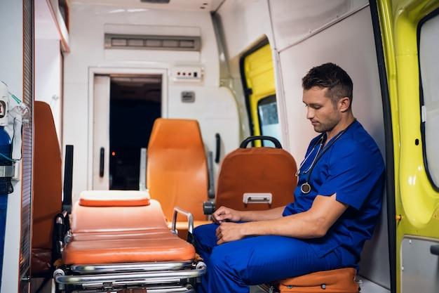 Corpsman in een blauwe uniform zitten in een ambulance auto denken
