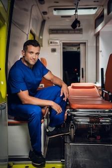 Corpsman in een blauwe uniform zitten in een ambulance auto glimlachen