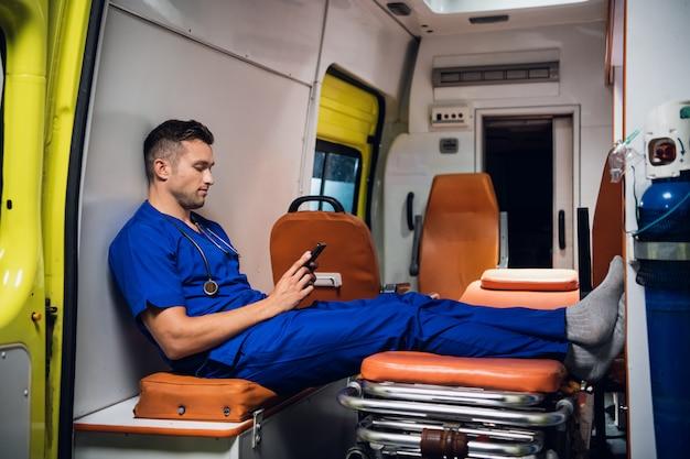Corpsman in een blauwe uniform zitten in een ambulance auto met smartphone