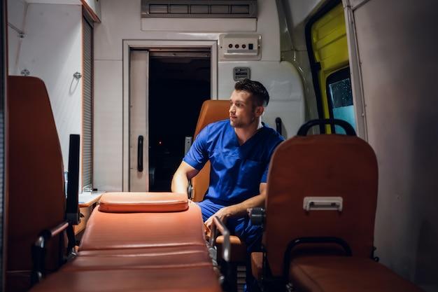 Corpsman in een blauwe uniform zitten in een ambulance auto wegkijken