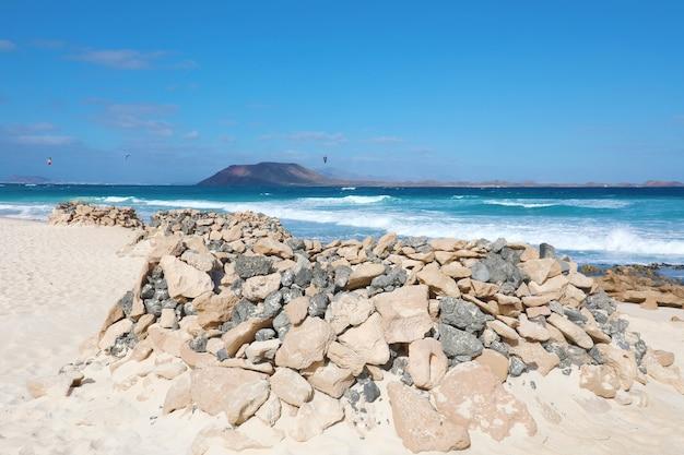 Corralejo dunas strand met stenen schuilplaatsen in fuerteventura, canarische eilanden