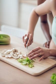 Correct ontbijt. nette slanke handen van blanke vrouw die champignons en greens hakken op het keukenoppervlak, gezichten zijn niet zichtbaar