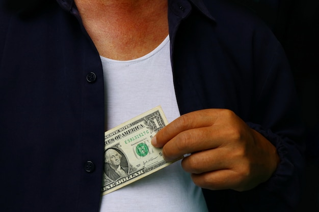 Corruptie. mens die geld in kostuumjasje zet