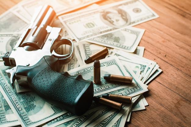 Corruptieconcept, met geweren en dollarrekeningen die op houten raad worden geplaatst.