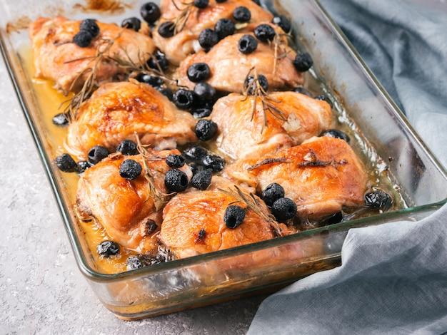 Corsicaanse kippendijen met rozemarijn, zwarte olijven, knoflook in citroensap en wijn. kippenbenen in oven op grijze concrete achtergrond worden gekookt die. gebakken kippenpoot in hittebestendig glas. kopieer ruimte
