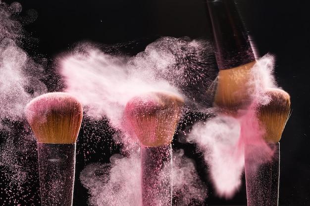 Cosmetica borstel en explosie licht roze kleurrijke make-up poeder zwarte achtergrond
