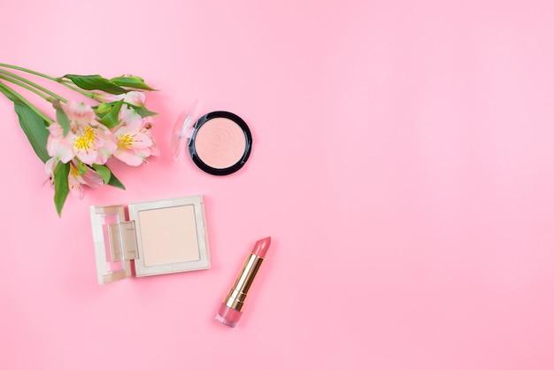 Cosmetica en bloemen op een roze achtergrond