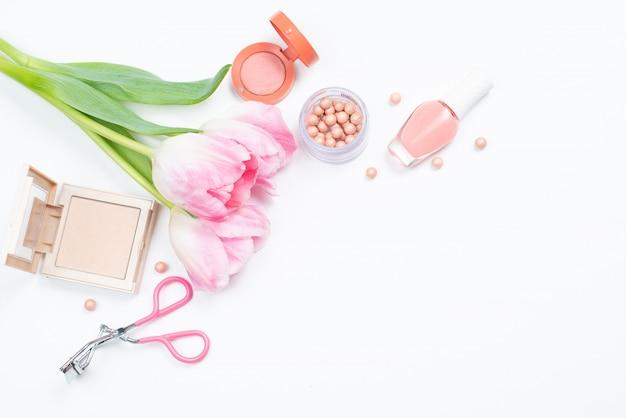 Cosmetica en bloemen op een witte achtergrond met ruimte voor tekst