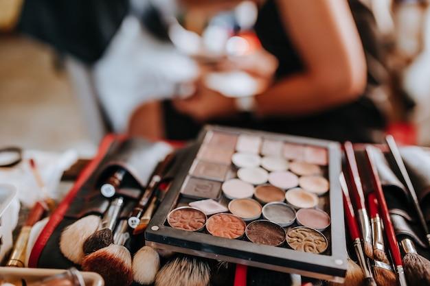 Cosmetica en make-upborstels liggen tijdens het werk van de visagist