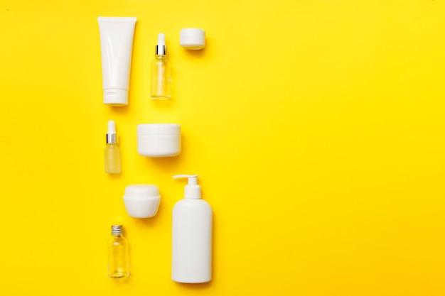 Cosmetica flessen op heldere gele achtergrond, bovenaanzicht, kopie ruimte. bespotten. witte potten, badaccessoires. gezichts- en lichaamsverzorging concept.