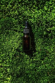 Cosmetica in een fles en etherische oliën op mos. natuurlijke kuuroord. selectieve aandacht. natuur.