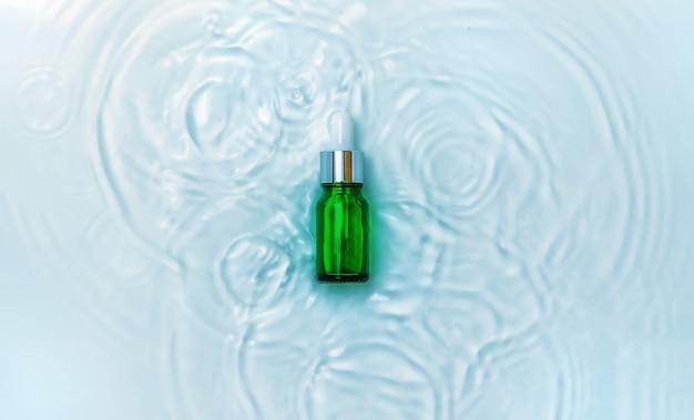 Cosmetica in een fles in water, huidhydratatieconcept. hyaluronzuur. selectieve aandacht. natuur.