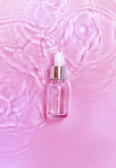 Cosmetica in een fles in water, huidhydratatieconcept. hyaluronzuur. selectieve aandacht.