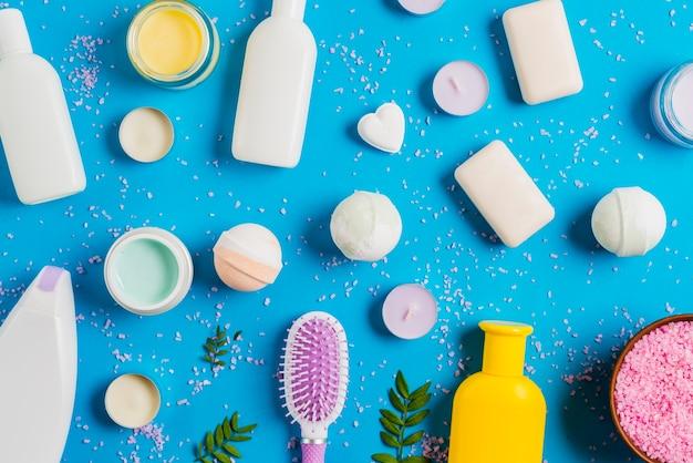Cosmetica producten en verspreid himalaya zout op blauwe achtergrond