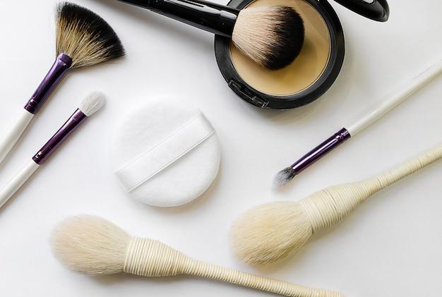 Cosmetica van het merk. mineraal compact poeder, spons en verschillende borstels voor toepassing, geïsoleerd op een witte achtergrond. selectieve aandacht.