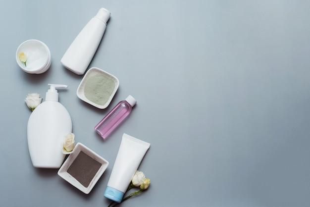 Cosmetica van natuurlijke ingrediënten en bloemextracten op een grijze achtergrond