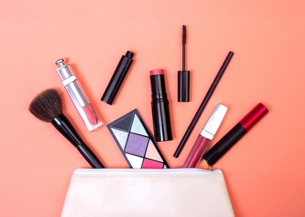 Cosmetica vielen uit de make-uptas op een koraalachtergrond