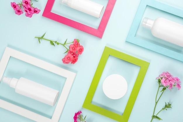 Cosmetica voor huidverzorging gezicht, lichaam, handen. witte lege cosmetische fles, buis, pot, bloemen in heldere frames op blauwe achtergrond. creatief cosmetisch schoonheidsconcept. mockup bovenaanzicht.