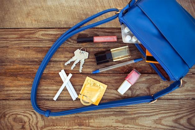 Cosmetica, vrouwelijke accessoires, anticonceptiepil, sigaret en condoom vallen uit de zak met handtassen