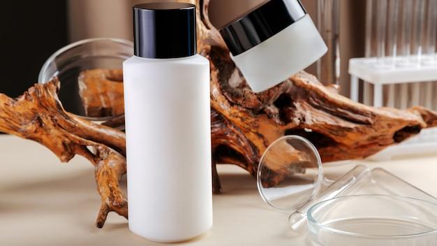 Cosmeticapakket voor huidverzorging. crème reinigingsmiddel kit voor huidverzorging op een beige achtergrond kleur met hout, laboratoriumglaswerk. huidverzorgingscosmetica set mock-up productfotografie. natuurlijk eco hout lange webbanner
