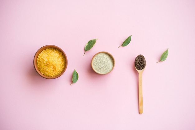 Cosmetisch badzout, druivengomaj voor het gezicht, koffiescrub voor het lichaam op een roze achtergrond.
