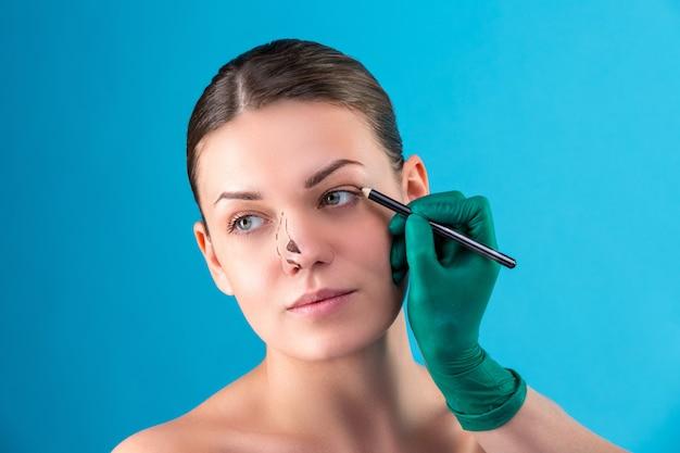 Cosmetisch chirurg die vrouwelijke cliënt in bureau onderzoekt. arts tekent lijnen met een marker, het ooglid voor plastische chirurgie, ooglidcorrectie. chirurg of schoonheidsspecialisthanden wat betreft vrouwengezicht. neuscorrectie