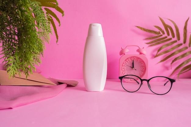 Cosmetisch fles minimalistisch concept idee op roze achtergrond met wekkerdecoratie, bladeren en glazen