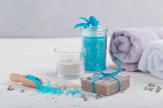 Cosmetisch kleipoeder, zelfgemaakte kleizeep en blauw badzeezout op witte achtergrond. gezichtsverzorging, lichaamsverzorging en spa-concept.